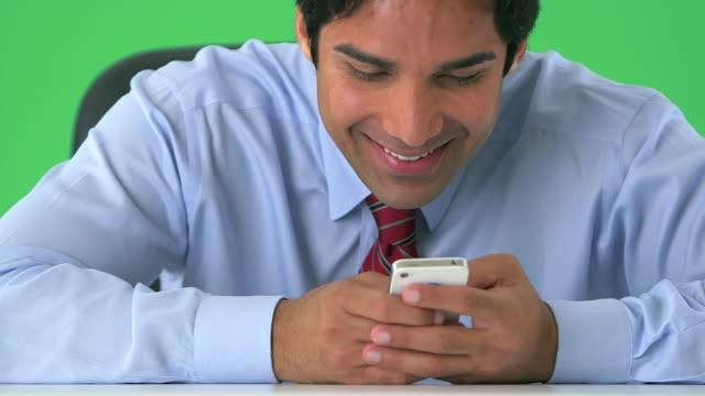 vidéos et rushes de east indian businessman texting on greenscreen - message sms