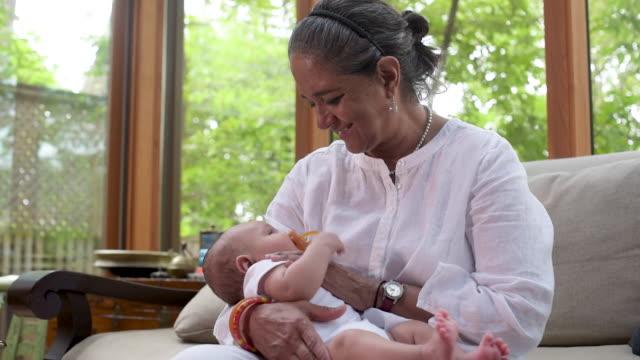 east indian grandmother holding newborn baby - 生後1ヶ月点の映像素材/bロール