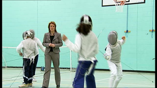 vídeos y material grabado en eventos de stock de east london club trains 2012 olympic hopefuls; reporter to camera as young people engage in fencing match reporter wearing fencing mask and holding... - en guardia