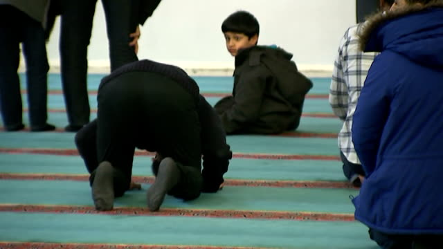 vídeos de stock e filmes b-roll de east london mosque launch event and interview int gvs of men in library area / men removing their shoes / men praying - remover