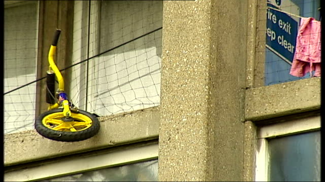 vídeos de stock, filmes e b-roll de poplar ext general view of exterior of robin hood gardens housing estate child's bike hanging off balcony housing block seen beyond flowers in f/g... - árvore de folha caduca