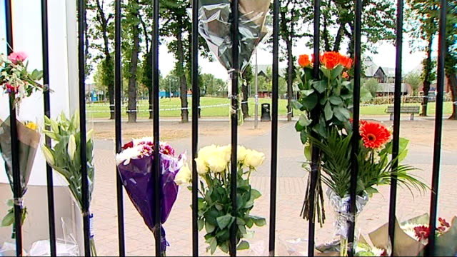 east london: walthamstow: ext metropolitan police officers and floral tributes at entrance to bus station police cordon tape at murder scene flowers... - white点の映像素材/bロール