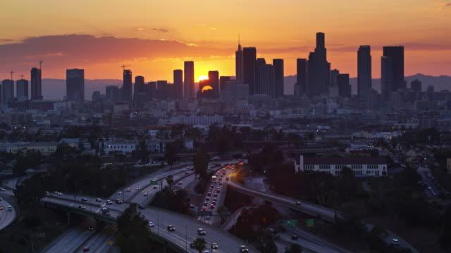 East Los Angeles Interchange avec soleil couchant derrière DTLA Skyline - vue aérienne