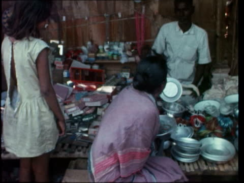 vídeos y material grabado en eventos de stock de east pakistan refugees b 550pm salt lake camp cms woman by tra of rice bv another by cooking pot ms woman and child inside ms three boys on floor... - calcuta