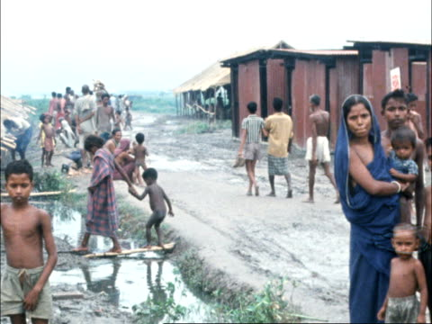 east pakistan refugees in dum dum camp:; india: calcutta: ext pan refugees in camp l-r: 2 children out of flood water and up bank: pan flood water... - pakistan stock videos & royalty-free footage