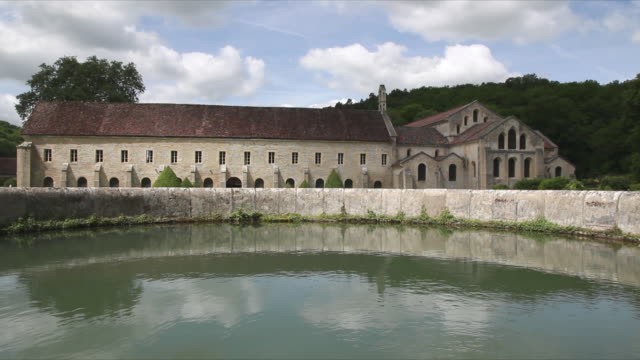 WS East side of Abbey of Fontenay: dormitory and church, pool of water in garden in foreground / Burgundy, France
