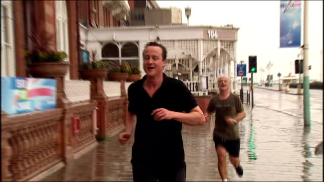 east sussex: brighton: ext cameron jogging along brighton seafront and away into hotel - 黒のシャツ点の映像素材/bロール