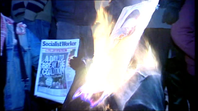 east sussex brighton ext protesters burning an effigy of prime minister david cameron in the street pull out various of demonstrators surrounding... - effigy stock videos & royalty-free footage