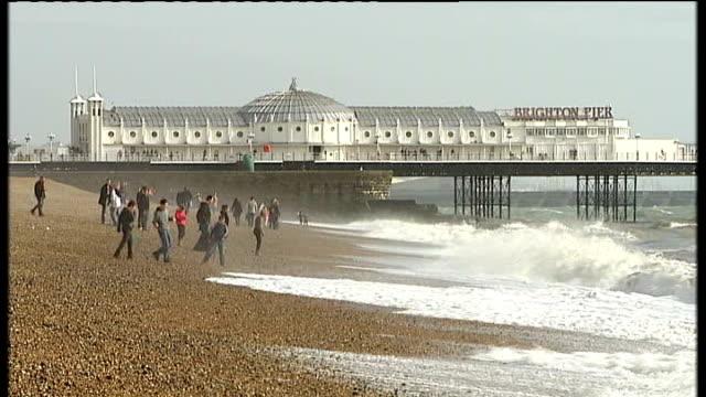 brighton: ext ruins of the west pier at sea seagull flying towards brighton pier people on brighton beach with brighton pier in background waves... - ブライトン パレスピア点の映像素材/bロール