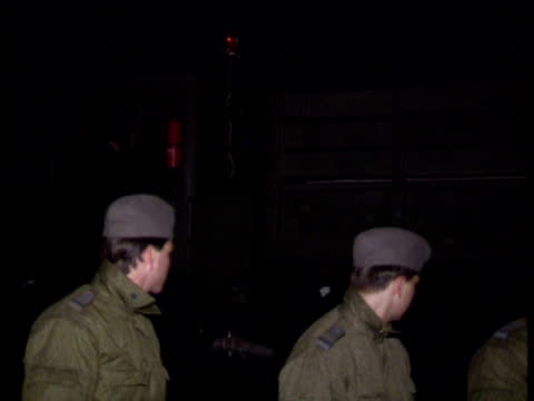 stockvideo's en b-roll-footage met ext / night hole in berlin wall east german soldiers standing around and a few west berliners watching as wall starts to come down soldiers watching... - vernieling