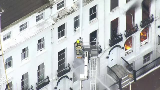 eastbourne hotel destroyed by fire; england: east sussex: eastbourne: ext air view / aerial firefighter on elevated platform hosing water onto the... - リチャード・パロット点の映像素材/bロール