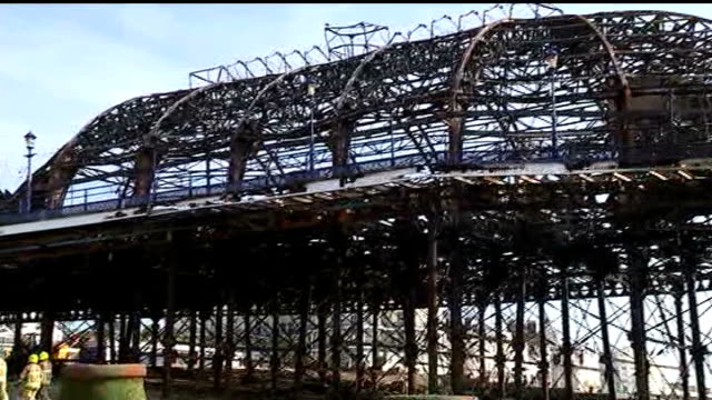 officials vow to rebuild pier; england: east sussex: eastbourne: ext various of firefighters hosing down fire-damaged eastbourne pier general view of... - リチャード・パロット点の映像素材/bロール