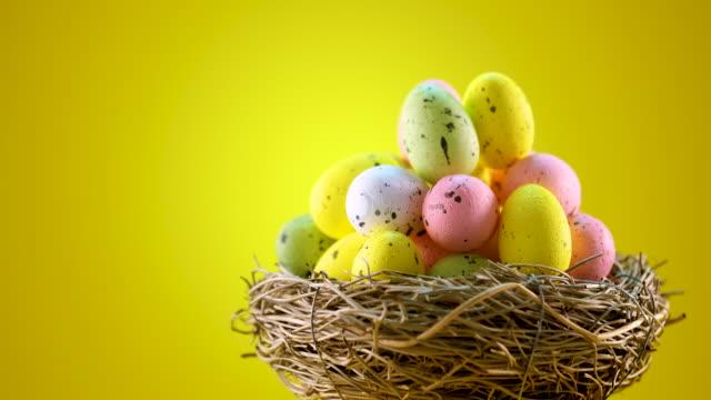 ostereier im nest auf gelbem grund - happy easter stock-videos und b-roll-filmmaterial