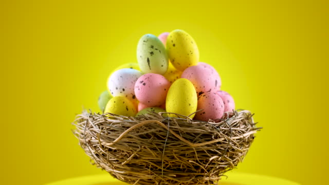 easter eggs in a nest on yellow background - easter stock videos & royalty-free footage