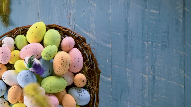 easter eggs in a nest with colorful feathers turning on blue wooden background - easter stock videos & royalty-free footage