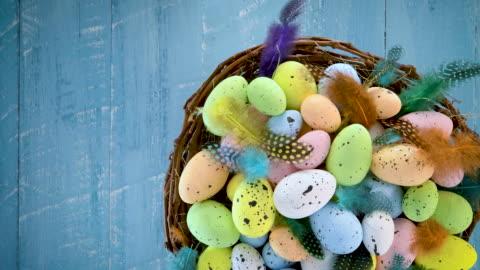 vídeos y material grabado en eventos de stock de huevos de pascua en un nido con plumas de colores que se vuelven sobre fondo de madera azul - pascua