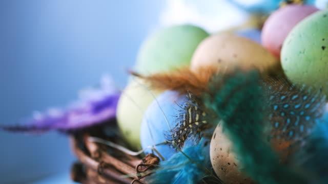 ostereier in einem nest mit fallinf bunte federn drehen auf blauen holzhintergrund - happy easter stock-videos und b-roll-filmmaterial