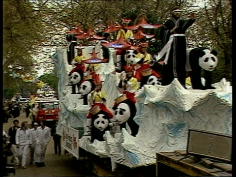 """easter parade; england: london: battersea park: zoom girls in floral jersey float panda float band """"st ivel"""" sof girl in crowd smiles... - battersea park stock videos & royalty-free footage"""