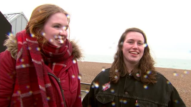 stockvideo's en b-roll-footage met easter weekend hit by bad weather england brighton people with umbrellas along wet seafront tilt down children wrapped in coats and scarves along... - wet