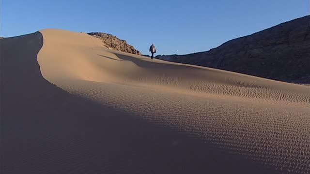 eastern desert. man walking down a sand dune. - extreme terrain stock videos & royalty-free footage