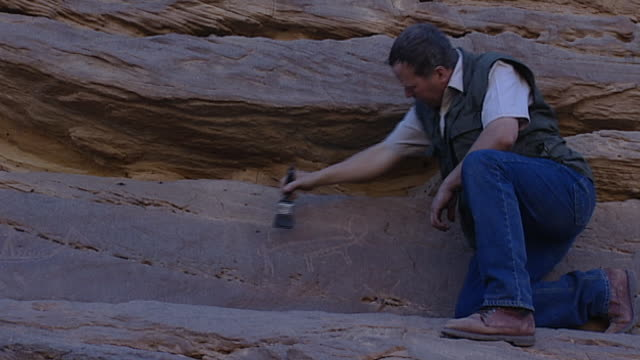 eastern desert rock art cu of an ancient animal petroglyph being cleaned by an archaeologist with a brush - extreme terrain stock videos & royalty-free footage