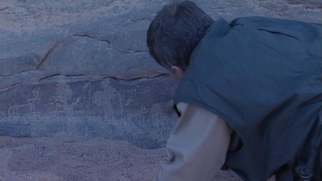 eastern desert rock art panrigth archaeologist removing brushing desert sand off to reveal ancient petroglyphs - brushing stock videos & royalty-free footage