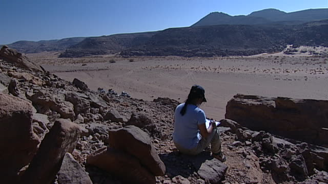 eastern desert. view of an archaeologist looking out across a wadi in the desert. - extreme terrain stock videos & royalty-free footage