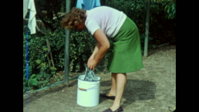 eastern german spa kühlungborn, boy is waiting with his mother and plays with a ball, family home area, woman washes clothes in a dirt bucket, boy is... - east germany stock videos & royalty-free footage