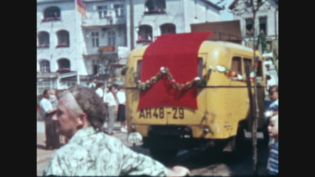 eastern germany in the city of kühlungsborn are people watching a big historical paggeant with horses cars old farming technics marching bands making... - 1959 stock-videos und b-roll-filmmaterial