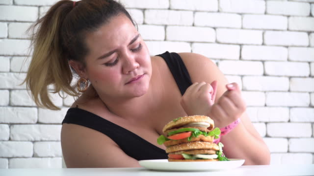 vídeos de stock e filmes b-roll de eat if you can eat, thai large build woman try to eat unhealthy food such as hamburger from inhibiting by measuring tape - unhealthy eating