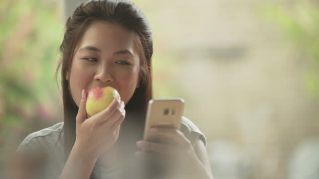 Eating apple with phone