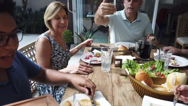 pov di mangiare barbecue con la famiglia - barbecue cibo video stock e b–roll