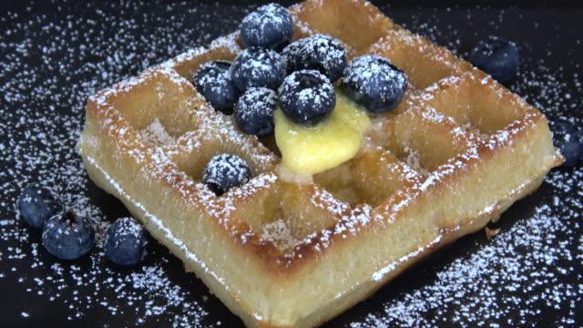 vídeos de stock, filmes e b-roll de comendo waffles belgas com xarope de maple, mirtilos e açúcar em pó - waffles