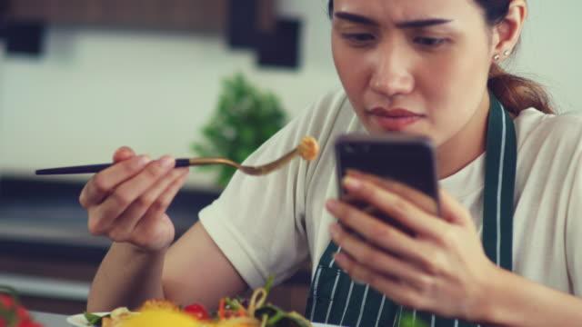 vídeos de stock, filmes e b-roll de comendo comida e telefone inteligente - jornal