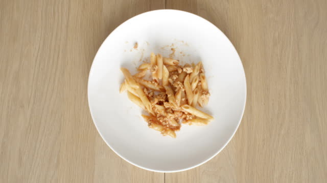 stockvideo's en b-roll-footage met eating food pasta bolognese top view of plate on a wooden table in time lapse - table top view