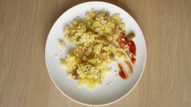 eating food rice top view of plate with ketchup rice and meat on a wooden table in timelapse - table top view stock videos & royalty-free footage