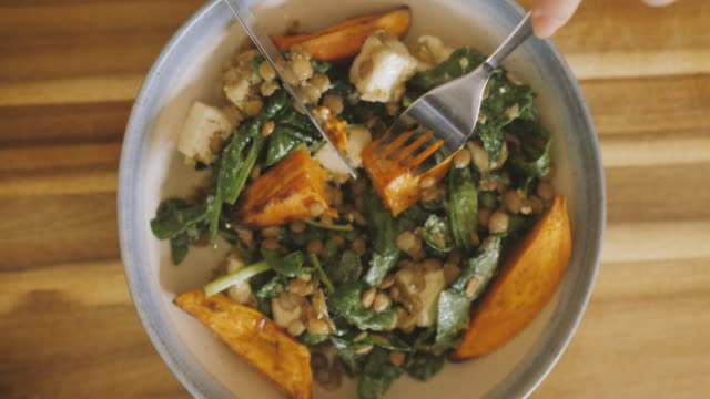 eating green lentil, spinach, and feta cheese salad with roasted sweet potato wedges - feta stock videos & royalty-free footage