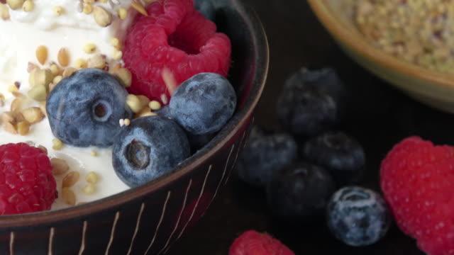 eating healthy greek yogurt with honey, raspberries, and blueberries - healthy eating stock videos & royalty-free footage