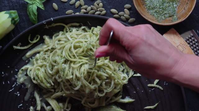 eating healthy zucchini noodles with pesto - pasta video stock e b–roll