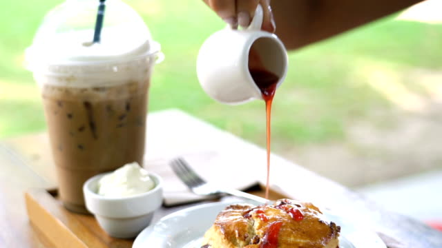 Eating iced coffee and scone with jam.