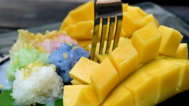 eating mango sticky rice, thailand food. - stick plant part stock videos & royalty-free footage