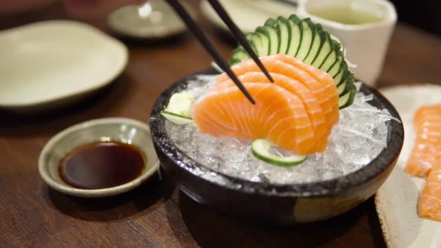 vídeos de stock e filmes b-roll de eating salmon sashimi. - salmão peixe