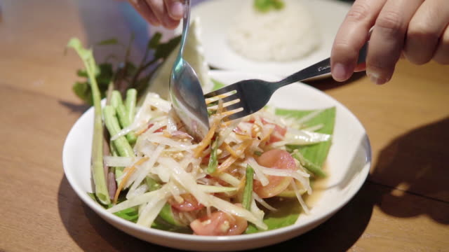eating som tam (green papaya salad) ,spicy salad made from shredded unripe papaya. - unripe stock videos and b-roll footage