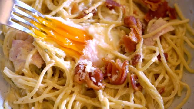 vídeos de stock, filmes e b-roll de comendo spaghetthi cabonara. - gema de ovo