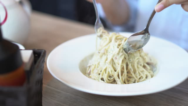 eating spaghetti carbonara with crispy becon. - italian food stock videos and b-roll footage