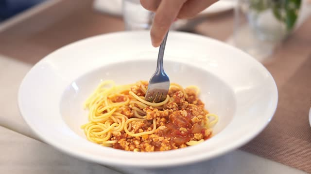 Eating spaghetti pork with tomato sauce.