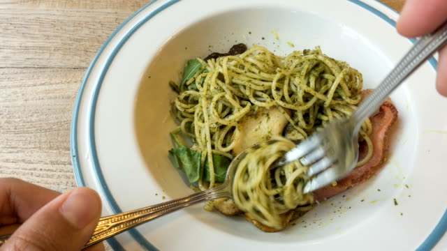 T/L eating spaghetti with pesto sauce and bacon