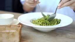 Eating spaghetti with pesto sauce, olive oil and basil with sausage.