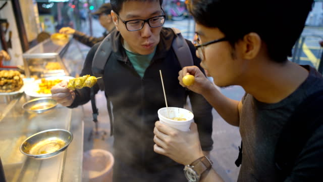 eating street food fish ball with friends in hong kong - chinese culture stock videos & royalty-free footage