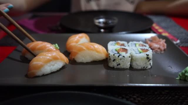 vídeos de stock e filmes b-roll de eating sushi with chopsticks in japanese restaurant. - sushi
